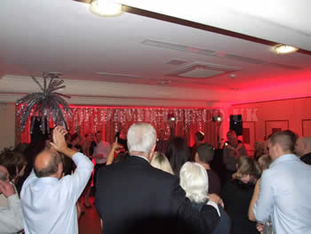All the wedding guests dancing with red venue lighting at Dukinfield Golf Club