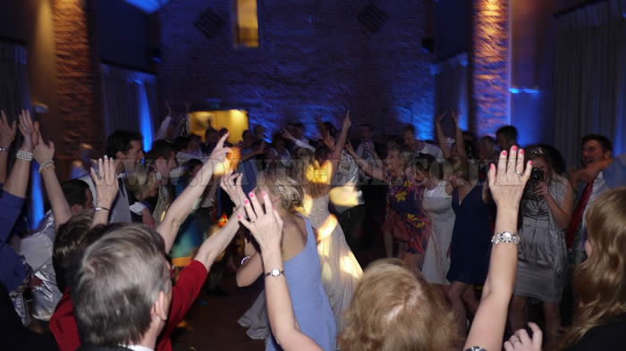Bride & Groom with all their guests with their hands in the air at Arley Hall